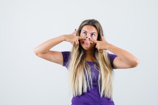 紫のtシャツを着て鼻に指を持って面白い金髪の女性。正面図。