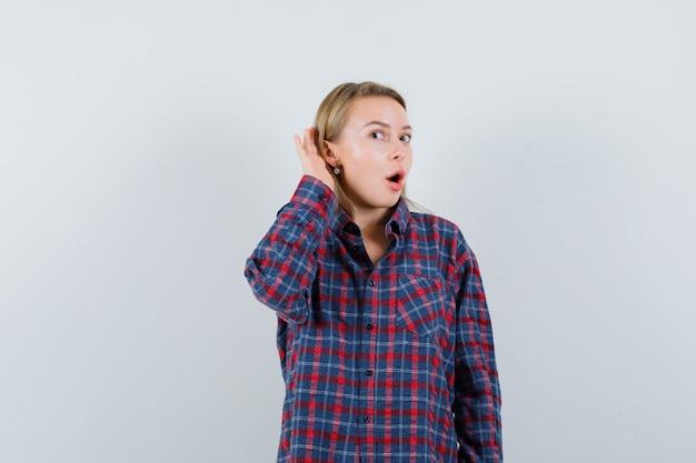 캐주얼 셔츠에 귀 뒤에 손을 잡고 호기심을 찾고 금발 아가씨. 전면보기.