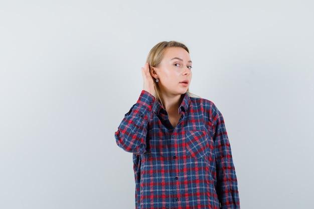 カジュアルなシャツを着て耳の後ろで手をつないで好奇心旺盛な金髪の女性。正面図。
