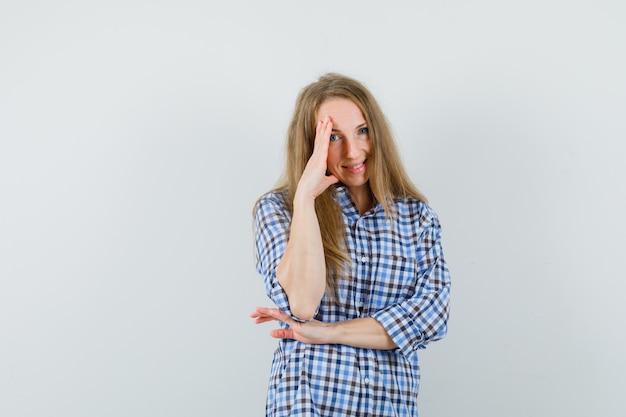 Signora bionda che tiene la mano sulla faccia in camicia e che sembra vergognarsi,