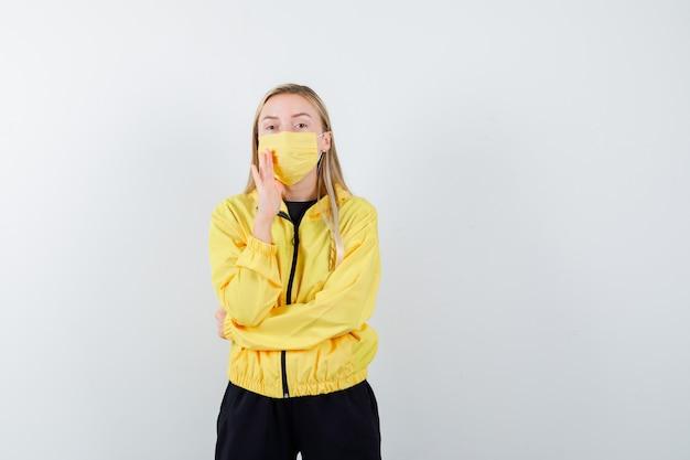 Блондинка держит руку возле рта, чтобы рассказать секрет в спортивном костюме, маске, вид спереди.