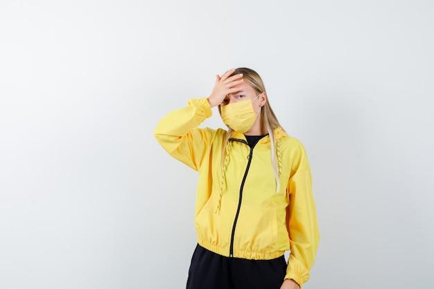 トラックスーツ、マスクで額に手を握り、悲しそうに見える金髪の女性。正面図。