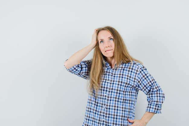 머리에 손을 잡고, 셔츠에 입술을 물고 우유부단 한 찾고 금발 아가씨.