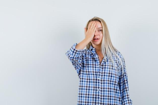 チェックのシャツを着て片方の目に手をつないで、前向きに見える金髪の女性