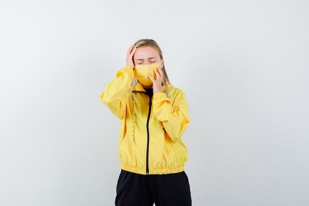 Signora bionda che tiene le mani intorno alla testa in tuta da ginnastica, maschera e sembra triste. vista frontale.