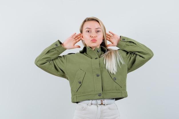 귀 뒤에 손을 잡고 금발 아가씨, 재킷, 바지, 전면보기에 입술을 삐죽.