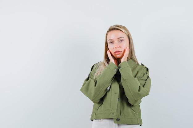 Signora bionda che tiene le mani sulle guance in giacca, pantaloni e dall'aspetto elegante, vista frontale.