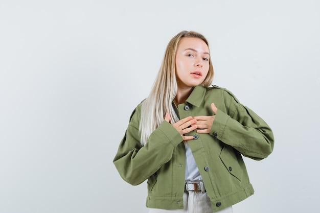 Signora bionda che tiene le mani sul cuore in giacca, pantaloni e sembra carina. vista frontale.