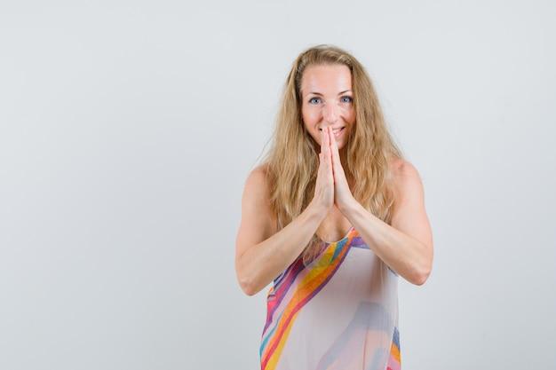Блондинка держится за руки в молитвенном жесте в летнем платье и смотрит с надеждой