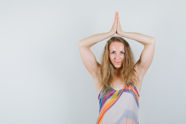 Blonde lady holding hands in namaste gesture over head in summer dress and looking hopeful