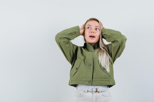 ジャケット、ズボンで耳に手をつないで、夢のような、正面図を探しているブロンドの女性。