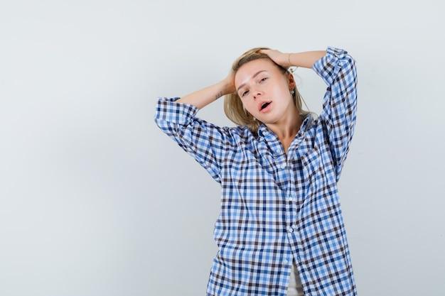 カジュアルなシャツで頭に手をつないで、繊細に見える金髪の女性