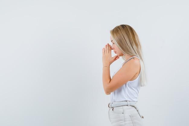 Signora bionda che si tiene per mano nel gesto di preghiera in singoletto, pantaloni e guardando speranzoso. .