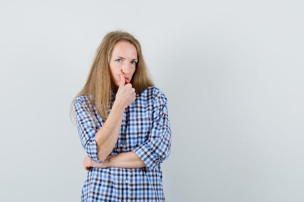Signora bionda che tiene il pollice vicino alla bocca in camicia e guardando dubbioso,