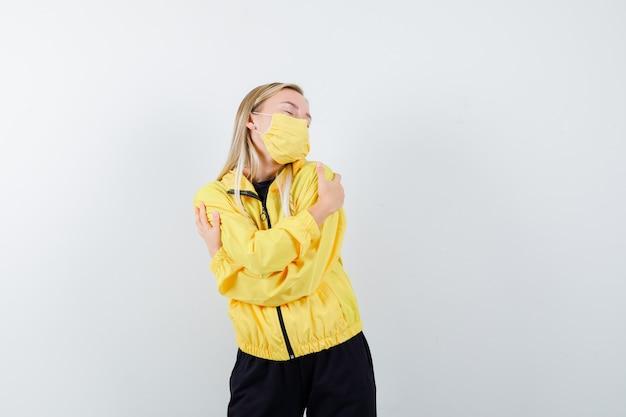 トラックスーツ、マスク、リラックスした表情で自分を抱き締める金髪の女性、正面図。