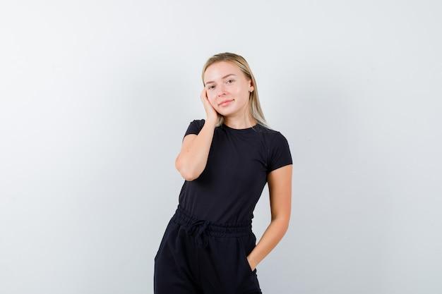 Блондинка в черном платье позирует с рукой по щеке и выглядит очаровательно, вид спереди.