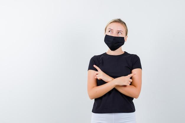 검은 색 티셔츠에 금발 아가씨, 양면을 가리키는 검은 마스크가 주저하고 있습니다.