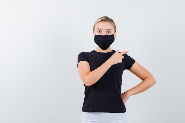 검은 티셔츠에 금발 아가씨, 고립 된 오른쪽을 가리키는 검은 마스크