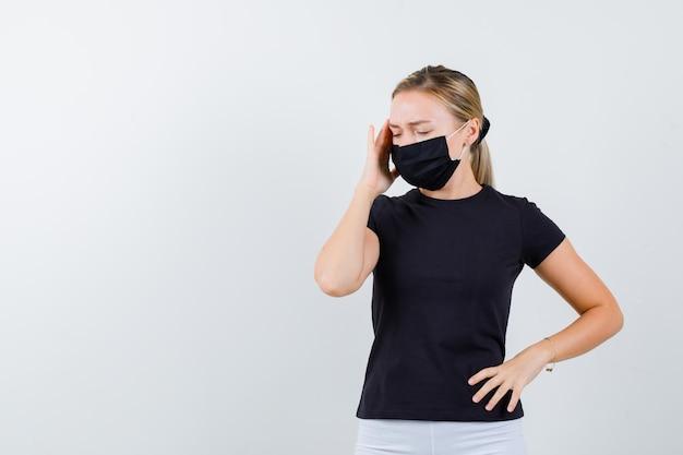 검은 티셔츠에 금발 아가씨, 검은 마스크가 사원을 문지르고 고통스러워 보입니다.