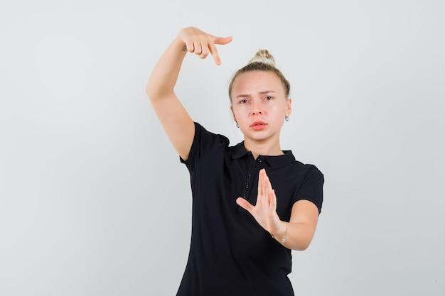 Блондинка в черной футболке, указывая на ее руку, протянулась и выглядела серьезной, вид спереди.