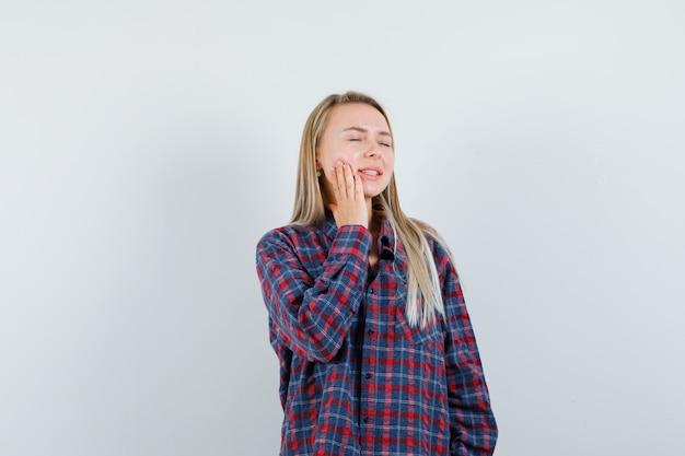 頬に手をつないで、夢のような、正面図を探しているカジュアルなシャツを着た金髪の女性。 無料写真