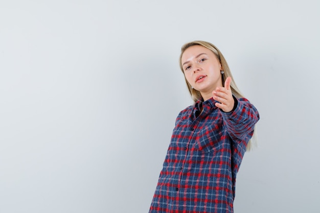 Блондинка в повседневной рубашке держит протянутую руку и выглядит весело, вид спереди.