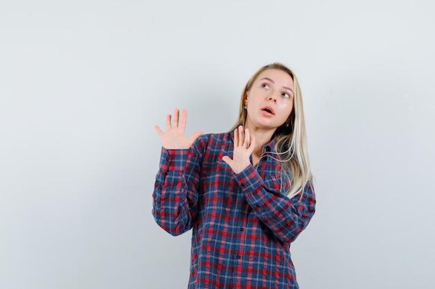 カジュアルなシャツを着た金髪の女性は、身を守るために手を保ち、怖がって、正面図を探しています。
