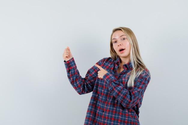 Блондинка в повседневной рубашке, указывая на что-то, делая вид, что держат, и выглядит веселой, вид спереди.