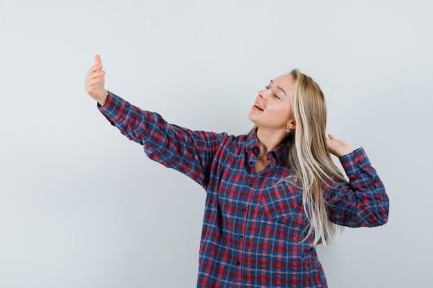 カジュアルなシャツを着た金髪の女性が、自分撮りをして陽気に見ながらポーズをとるふりをして、正面図。