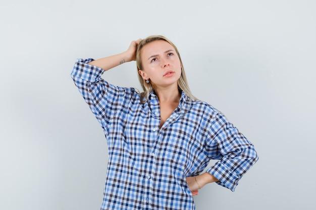 Блондинка в повседневной рубашке почесывает голову и смотрит задумчиво