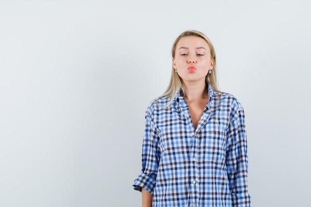 チェックシャツを着た金髪の女性が唇を折りたたんで見栄えを良くする