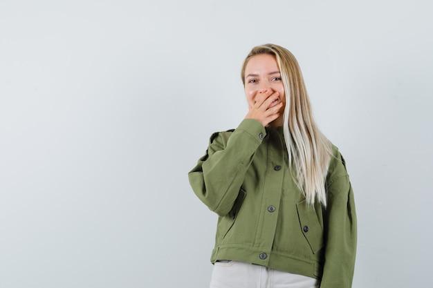 Блондинка в куртке, штаны, взявшись за рот и возбужденно, вид спереди.