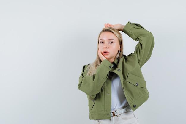 재킷에 금발 아가씨, 서 있고 유혹, 전면보기를 보면서 포즈 바지.