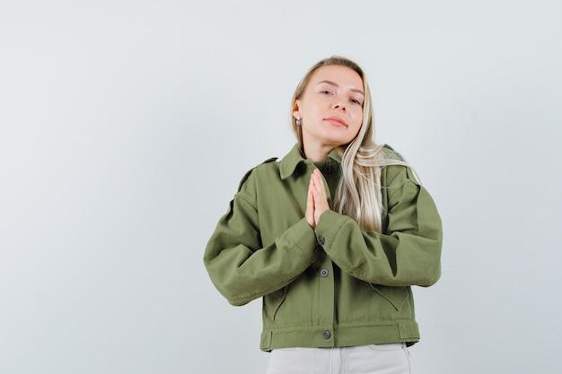 ジャケットの金髪の女性、ナマステのジェスチャーを示し、希望に満ちた、正面図を示すパンツ。