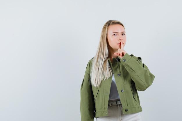 Блондинка в куртке, штанах показывает жест молчания и внимательно смотрит, вид спереди.