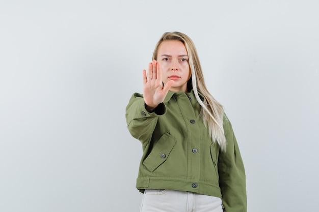 재킷에 금발 아가씨, 바지 중지 제스처를 표시하고 짜증, 전면보기를 찾고.