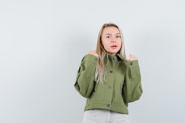 재킷에 금발 아가씨, 승자 제스처를 보여주는 바지 자신감, 전면보기.