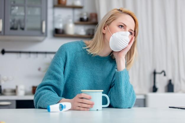 熱いお茶と台所のテーブルで温度計のカップとマスクで金髪の女性