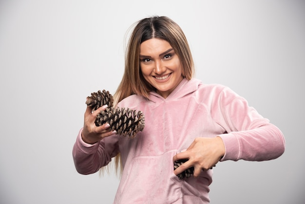 분홍색 셔츠를 입은 금발 아가씨는 오크 나무 콘을 잡고 긍정적이고 행복한 얼굴을 만듭니다.