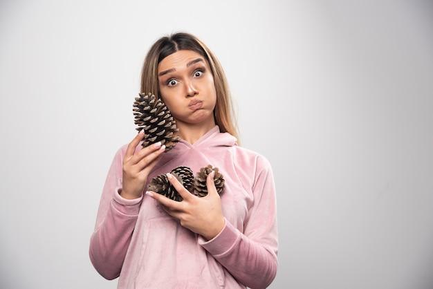 분홍색 셔츠를 입은 금발 아가씨는 손에 떡갈 나무 콘으로 어리석은 긍정적 인 얼굴을 만듭니다.