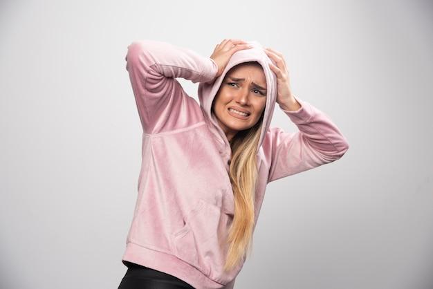 분홍색 셔츠에 금발 아가씨는 까마귀에 겁에 질리고 무서워하는 얼굴을 만듭니다.