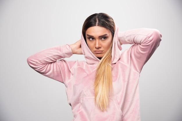 ピンクのスウェットシャツを着た金髪の女性は、パーカーで恐怖と恐怖の顔をします。
