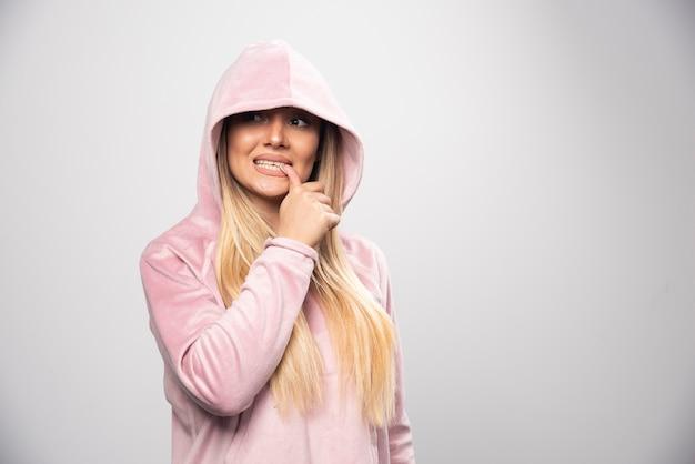 ピンクのスウェットシャツを着た金髪の女性が、頭にパーカーを着て楽しく前向きなポーズをとっています。