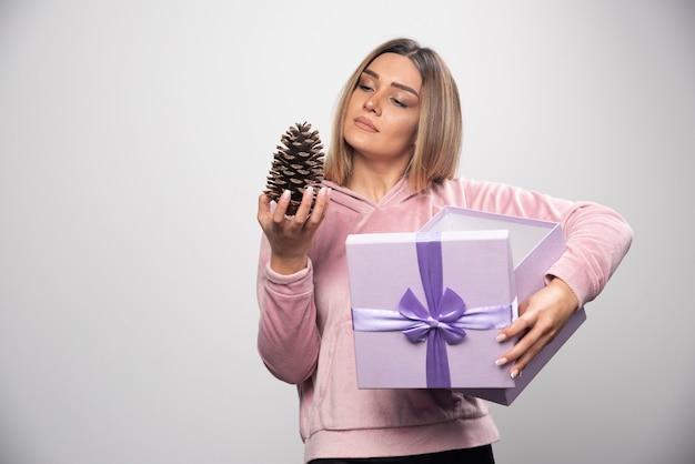 ピンクのスウェットシャツを着た金髪の女性は、ギフトボックスからオークの木の円錐形を取り出して幸せを感じます。