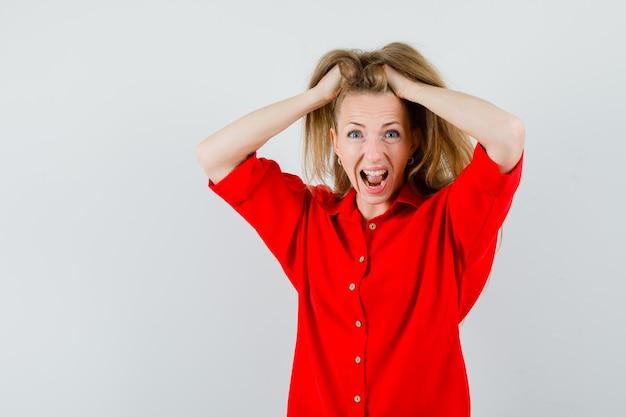 赤いシャツを着た金髪の女性が髪に手をつないで狂ったように見える、