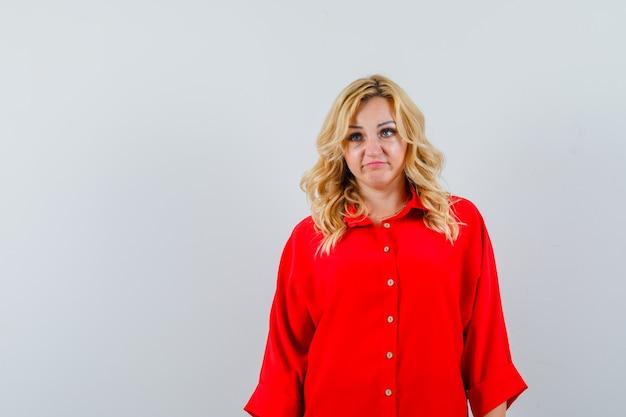 Блондинка в красной рубашке смотрит в сторону и грустно смотрит на место для текста