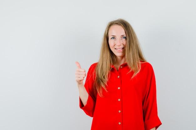 赤いシャツを着た金髪の女性が親指を立てて陽気に見える、