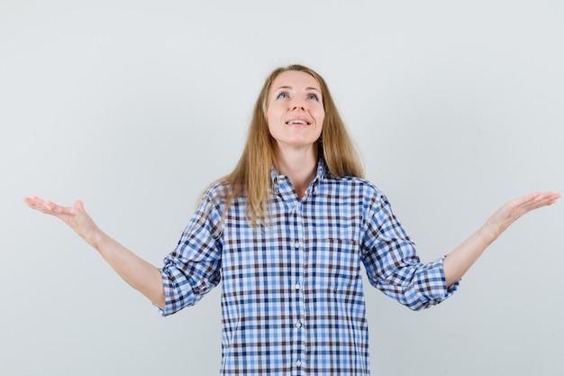 腕を広げ、見上げて感謝しているシャツを着た金髪の女性、