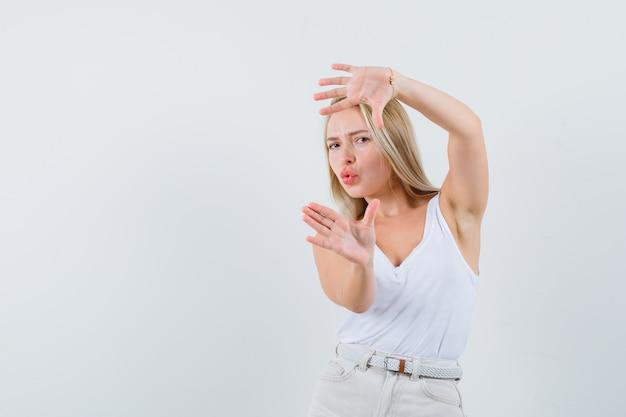 一重項のブロンドの女性、フレームジェスチャーを作成し、自信を持って見えるパンツ、正面図。
