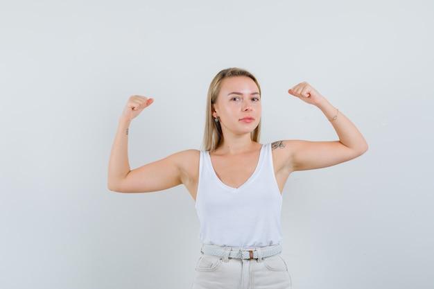 一重項の金髪の女性、腕の筋肉を示し、自信を持って見えるパンツ、正面図。